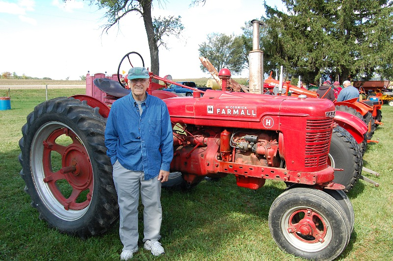Wilmer Bloy beside a Farmall H tractor