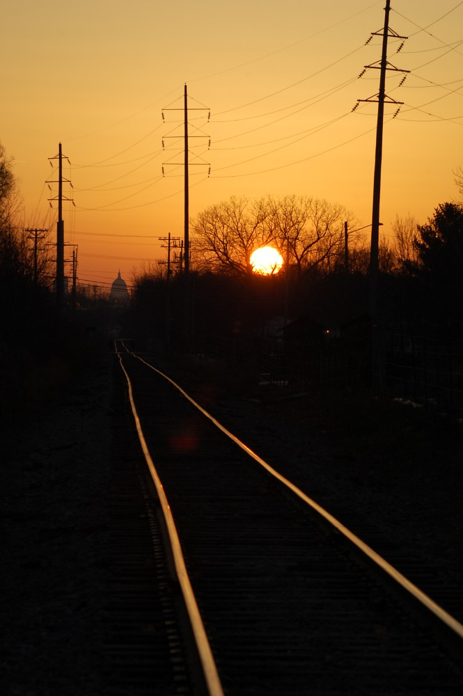 sun setting along railroad tracks to the capitol
