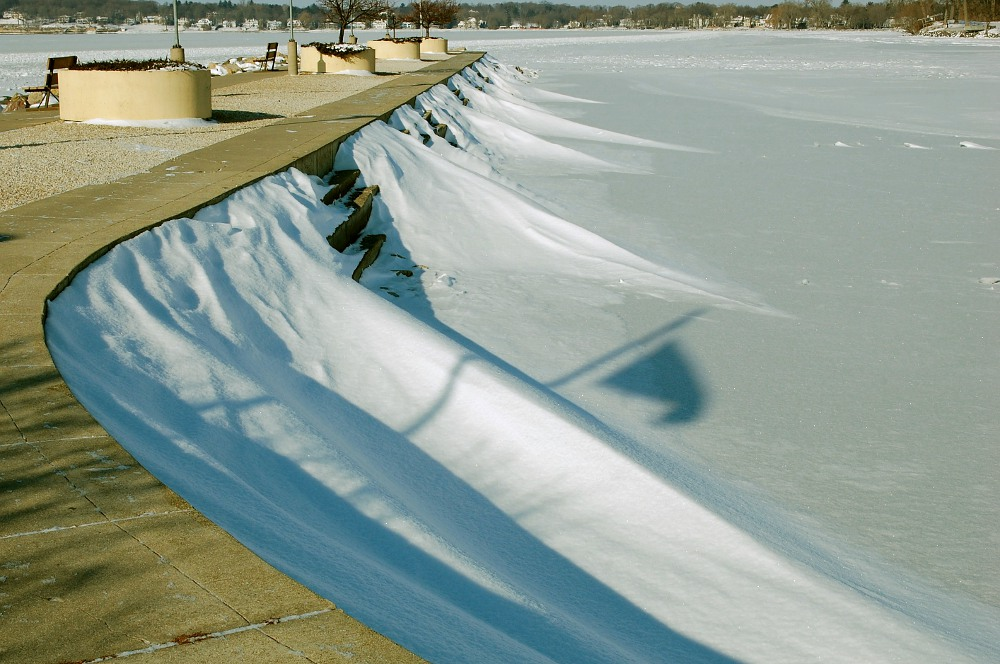 snow drifts along a dock