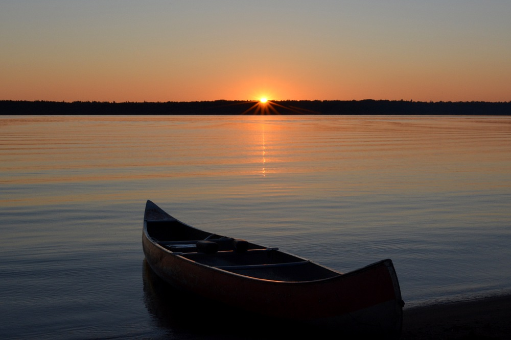 Canoe facing a setting sun