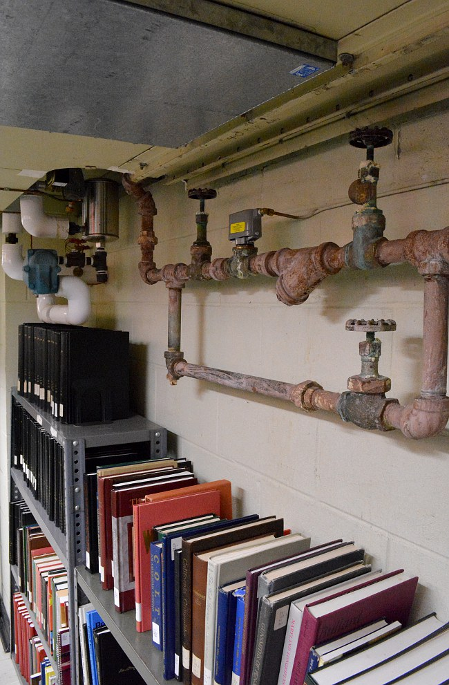 Bookshelves and corroded pipes