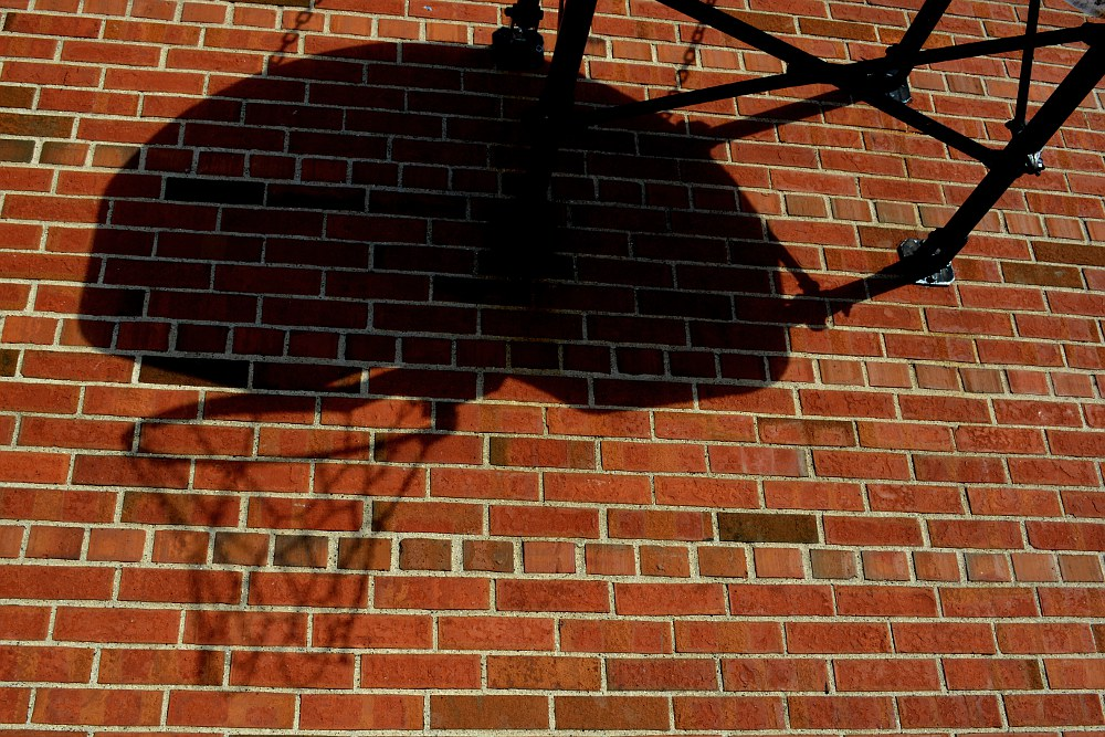 shadow of basketball backboard on a brick wall