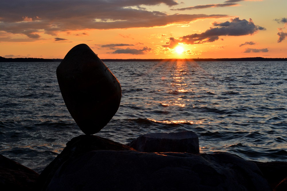 rock balanced in front of sunset