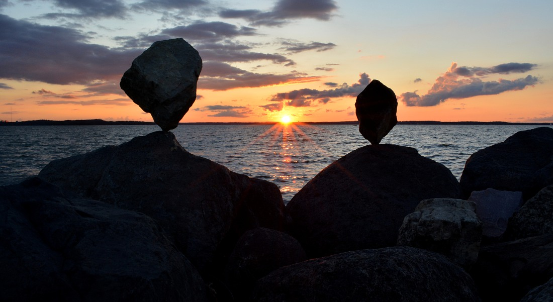 rocks balanced in front of sunset