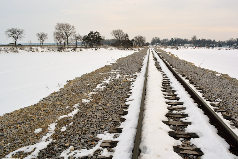 railroad tracks cross a frozen bay
