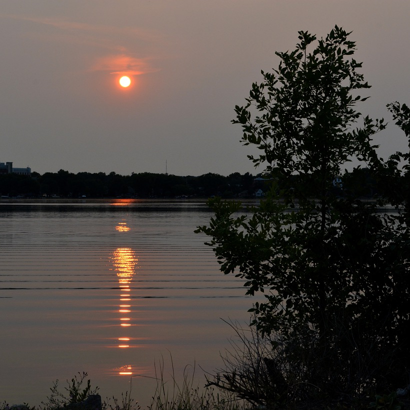 A red sun setting over Monona Bay