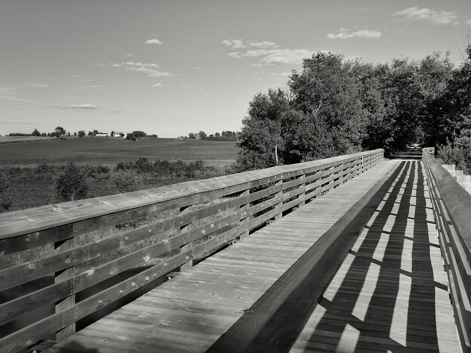 Shadows of the railings on a wooden bridge
