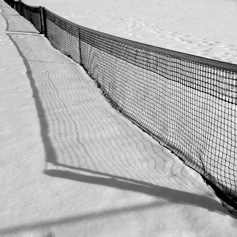 Tennis court nets cast shadows on the snow