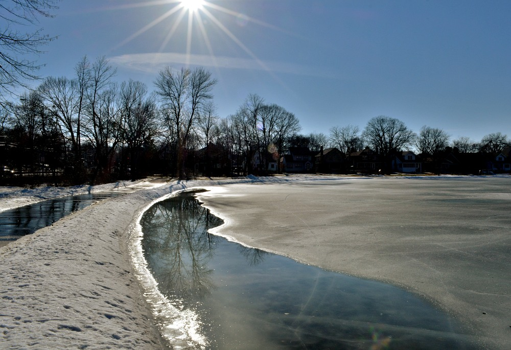 Sunshine melting the snow and ice on a lagoon