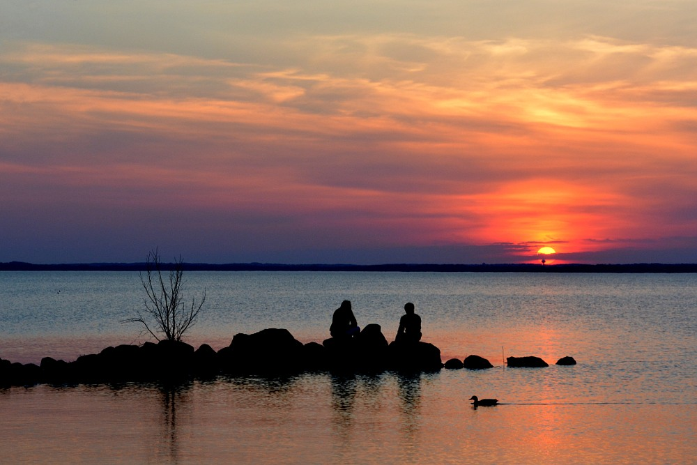 silhouette of two people watching the sunset over a lake