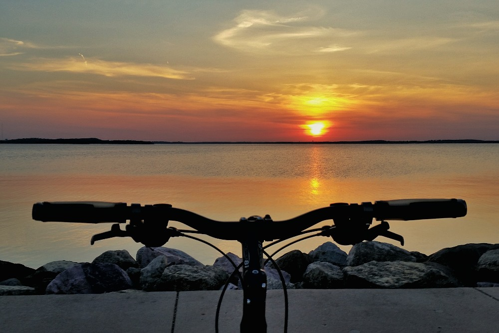 bicycle handlebars under a lakeside sunset