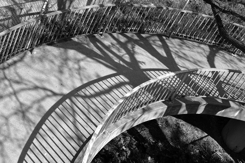 Shadows on a sidewalk overpass ramp