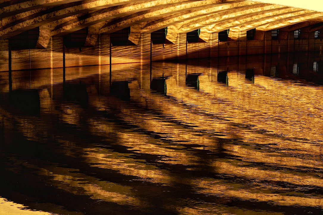 Reflections of the underside of a bridge in a river