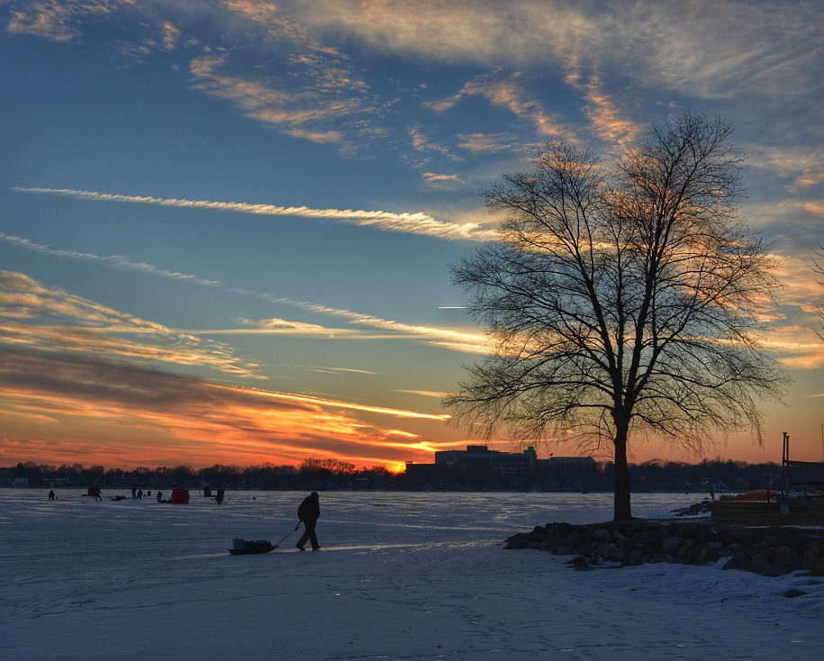 Ice fisherman leaves Monona Bay under a sunset sky