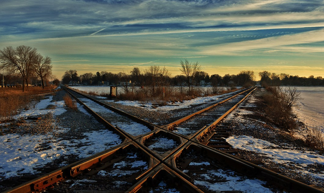 Railroad crossing under a late afternoon sky