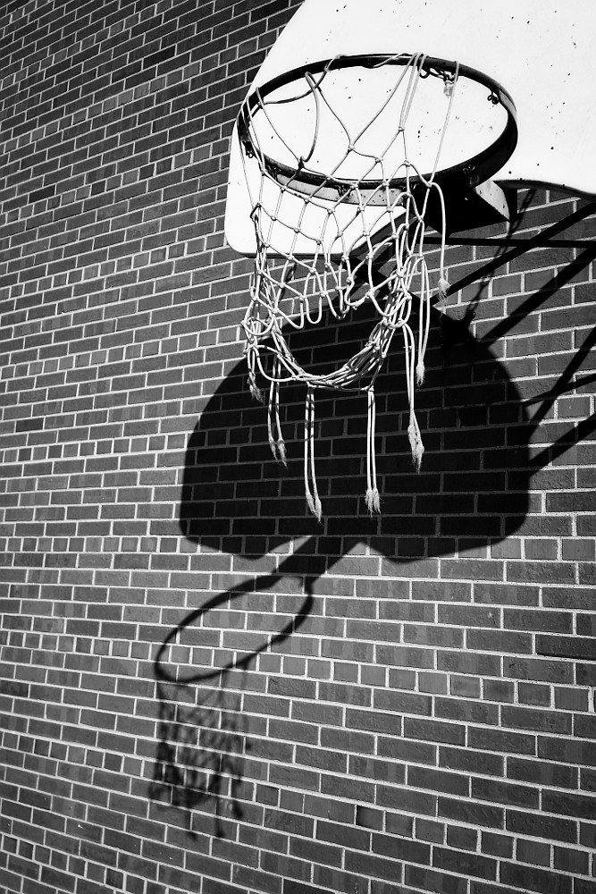Frayed and torn net hanging from a basketball hoop