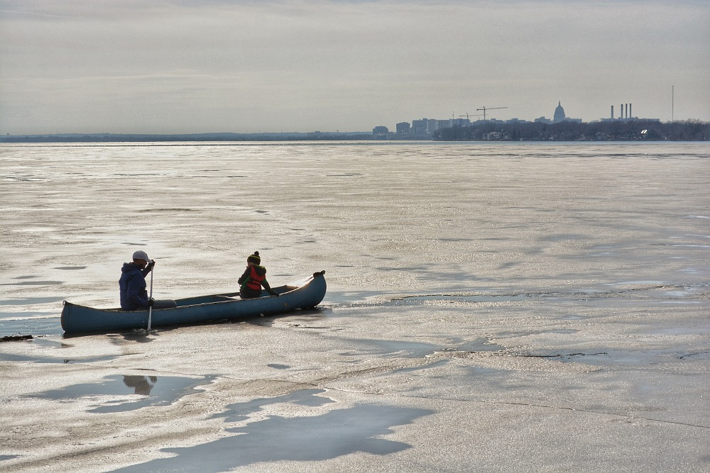 Canoe navigating a break in the ice on Lake Monona