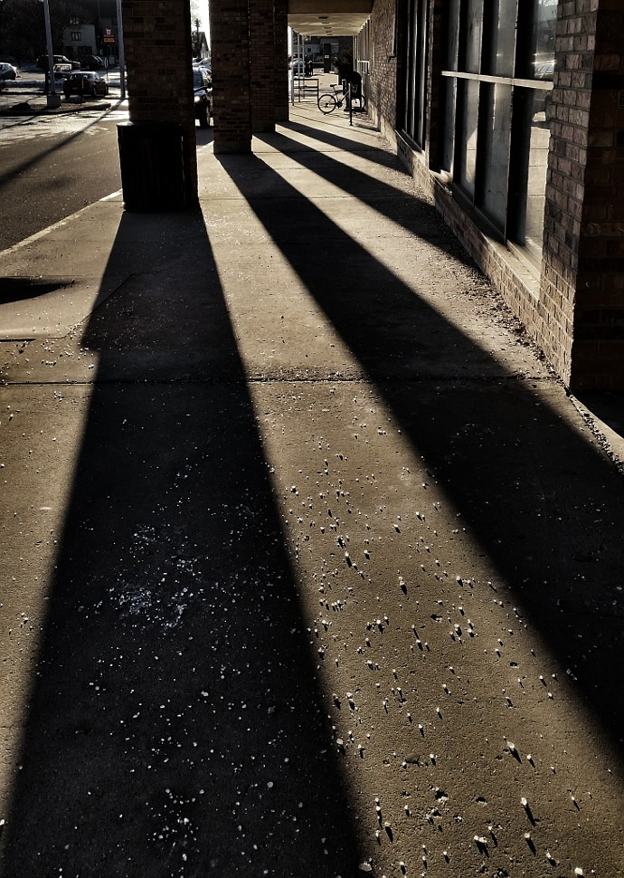 Long shadows from pillars cast on a salted sidewalk
