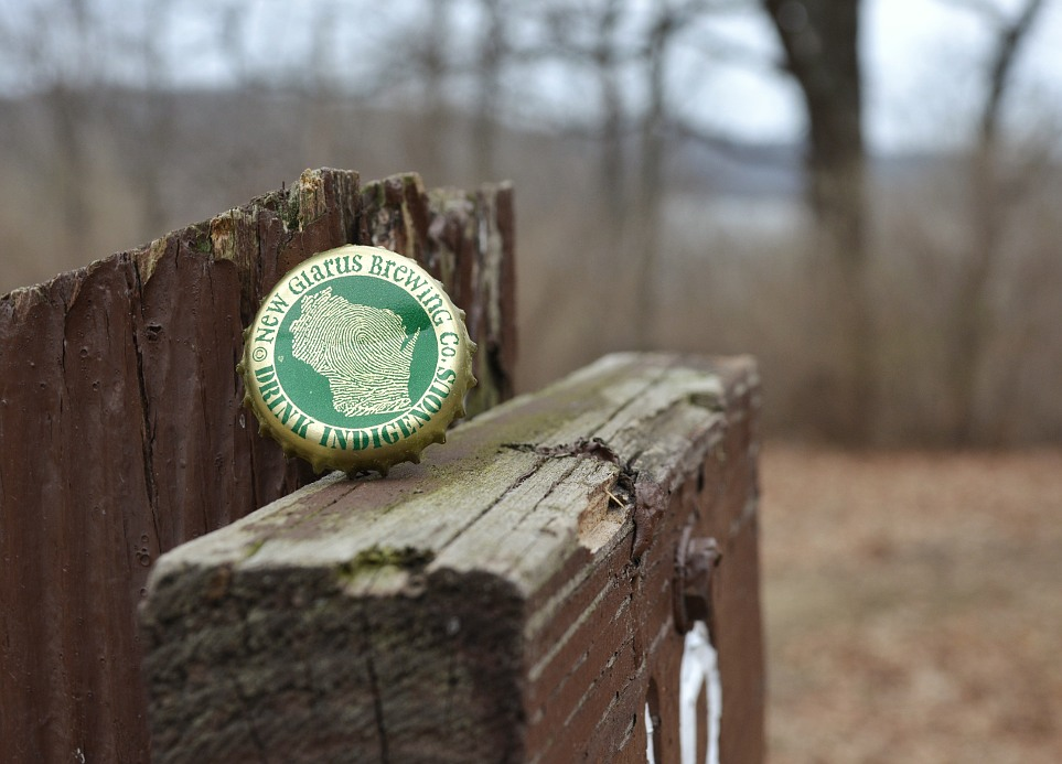 Beer bottle cap, resting on a hiking trail marker