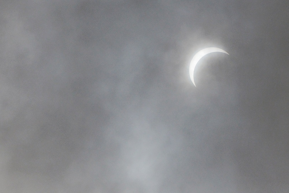 solar eclipse seen through clouds