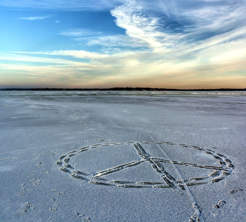 peace sign made with footprints in the snow on a frozen lake