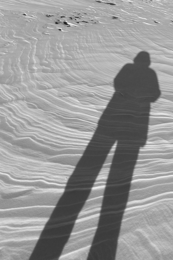 human shadow with snow patterns on a frozen lake