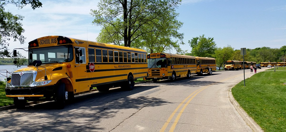 A line of school buses, parked along the drive of Vilas Park