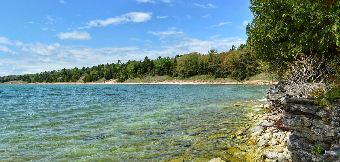 lakeshore with beach, trees, and limestone ledge