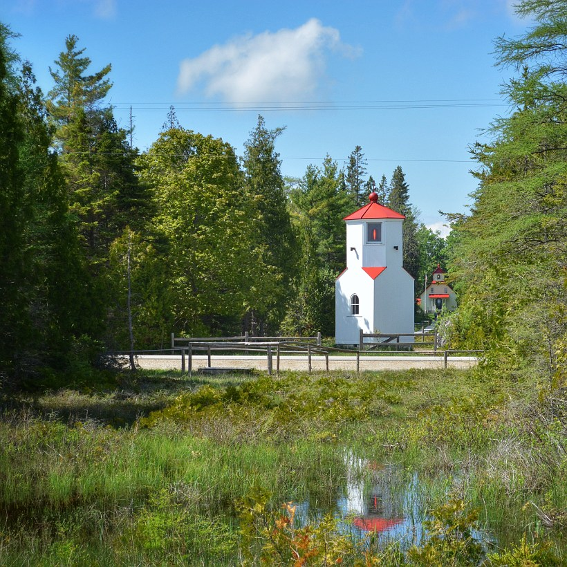 Range light surrounded by trees with keeper's house in the background