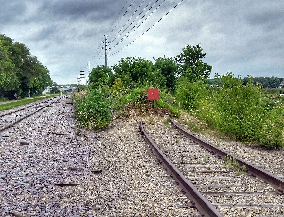 The end of a railroad spur, along side a mainline track