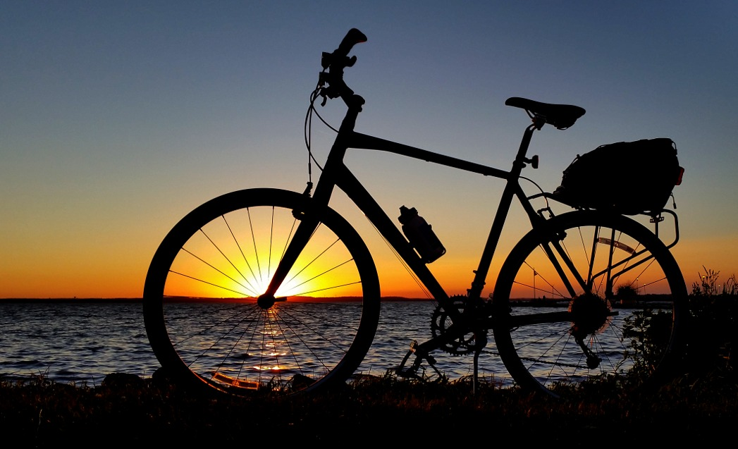 Silhouette of a bicycle in front of a lakeside sunset