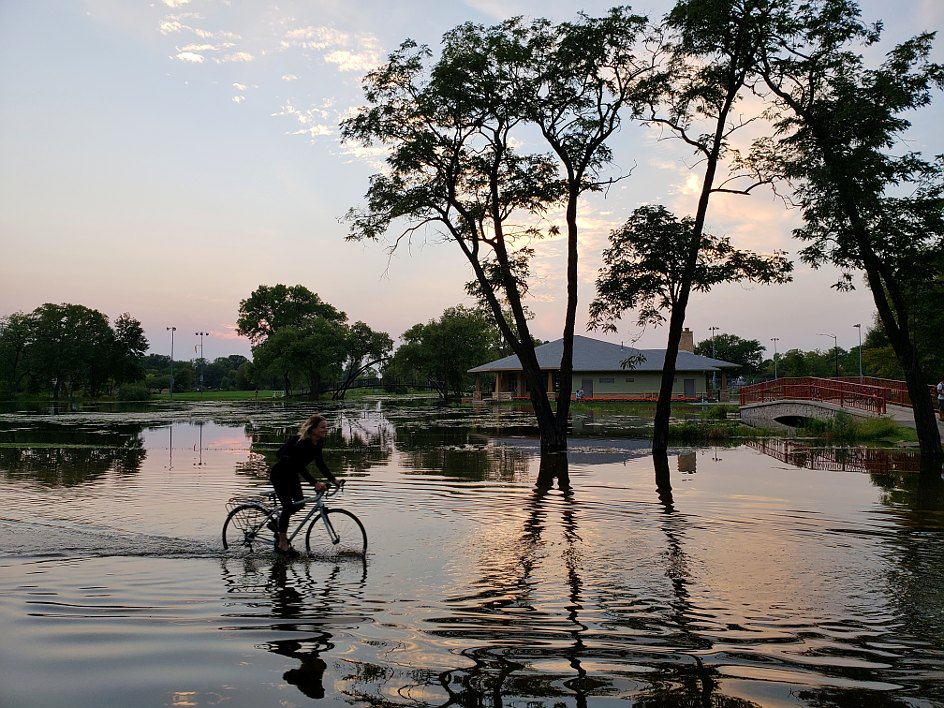bicyclist riding on a flooded street