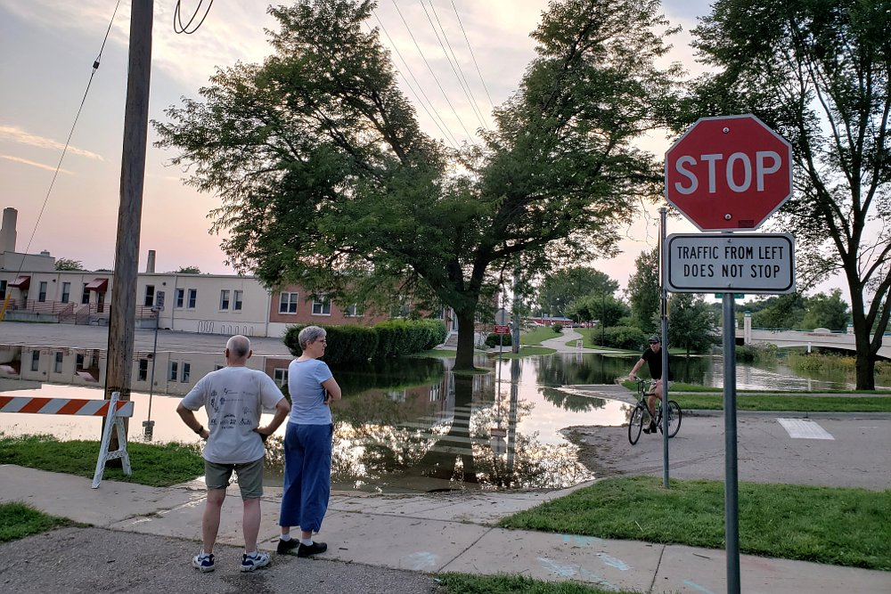 People standing next to a flooded street and trail