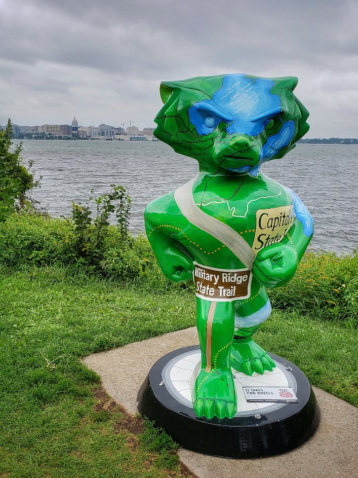 Front of a Bucky Badger statue painted with images of bike trails