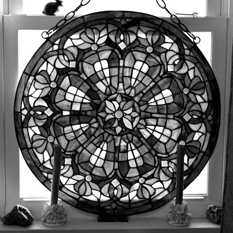 monochrome photo of a round stained glass hanging in a window