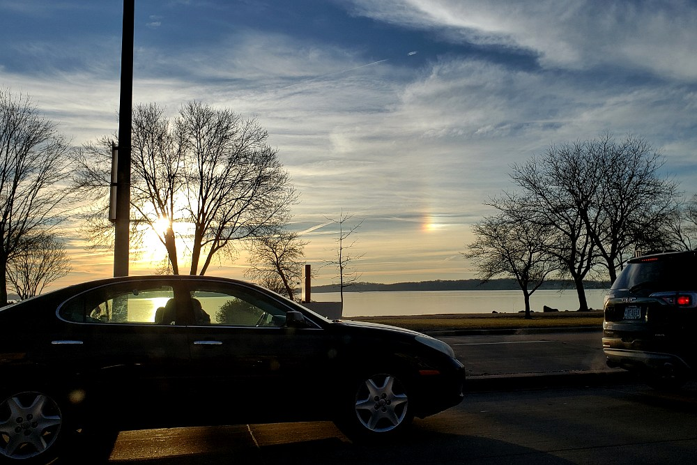 Automobile and trees in silhouette with the sun and a sun dog in a partly cloudy sky