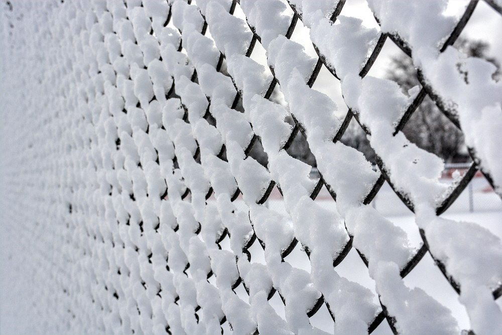 Snow stacked up on the wires of a chain link fence