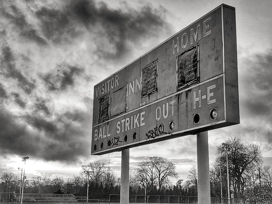 Old dilapidated baseball scoreboard in front of a cloudy sky