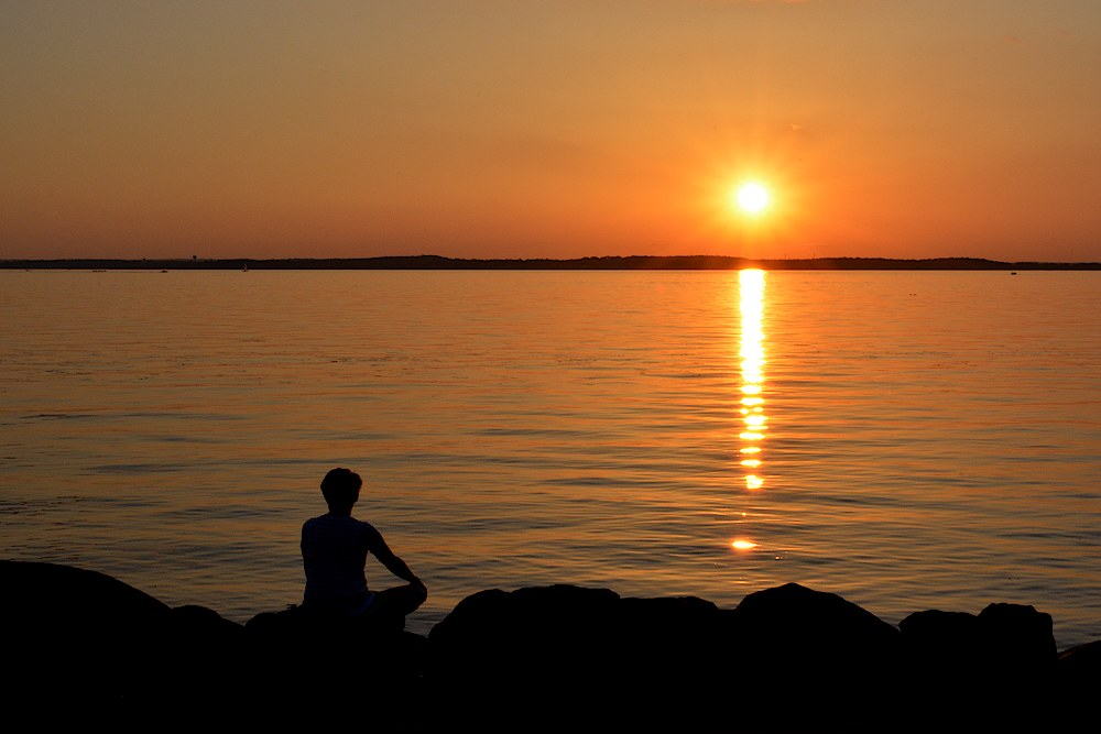 Silhouette of a woman sitting cross legged watching a sunset over a lake