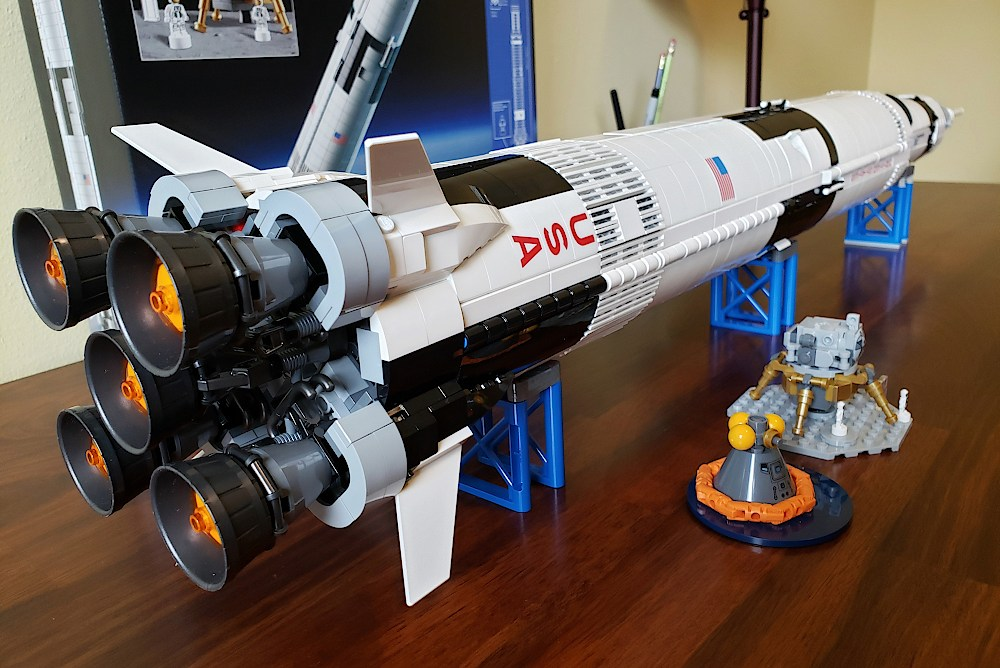 View from the base of a Saturn V rocket built with Legos, laying horizontally on a desk
