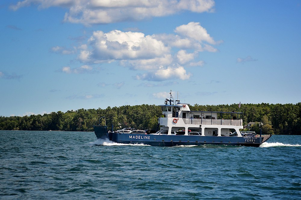 Ferry boat running in Lake Superior in front of a forested mainland