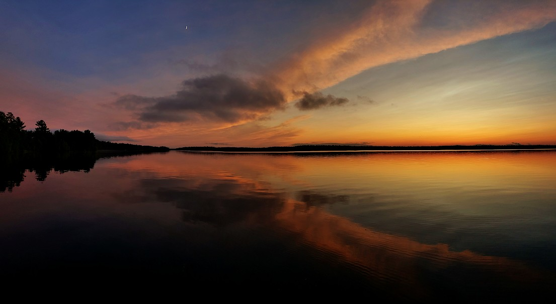 Orange and yellow colored clouds streaking across a dark blue sky reflected in a calm lake.