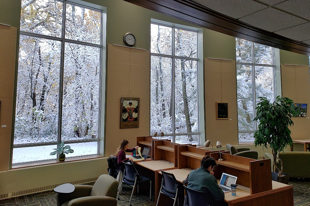 Two students study at desks in front of large windows with views of snow covered trees outside