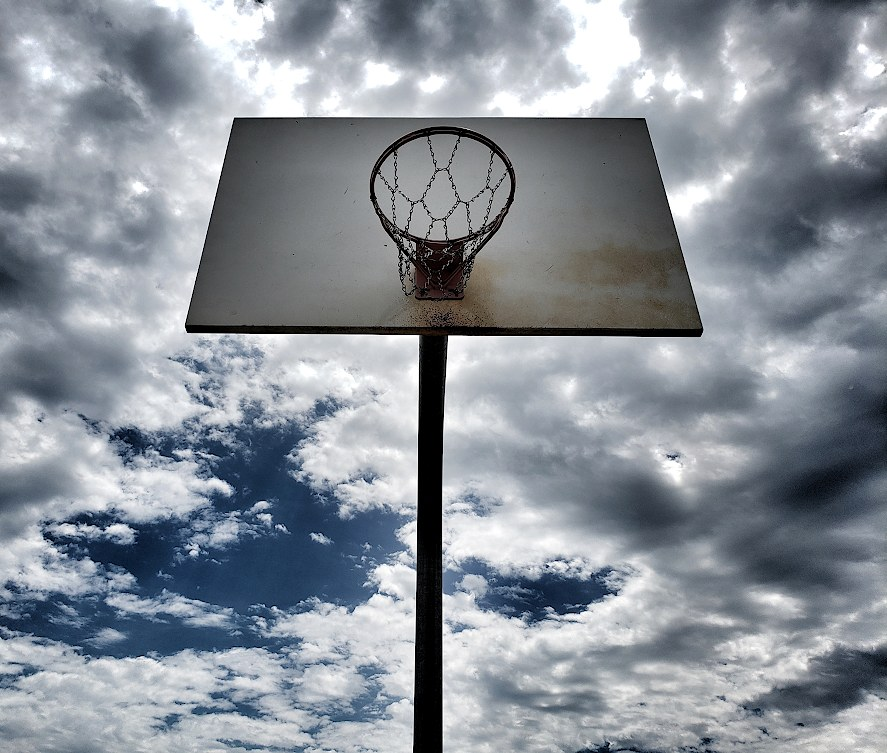 Looking up at a basketball hoop and backboard in front of a mostly cloudy sky