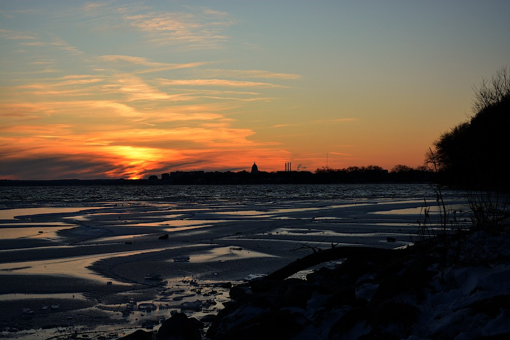 Sunset over a lake which is starting to freeze near the shore