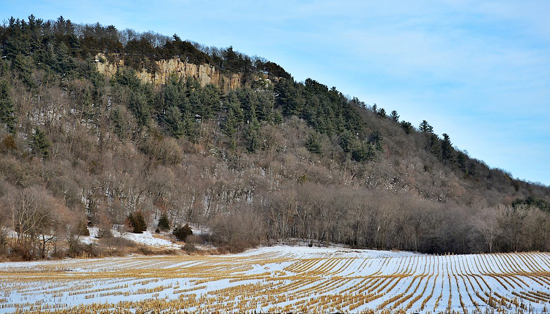 200 foot high hill with a rocky outcropping at the top and snow covered farm field in the foreground