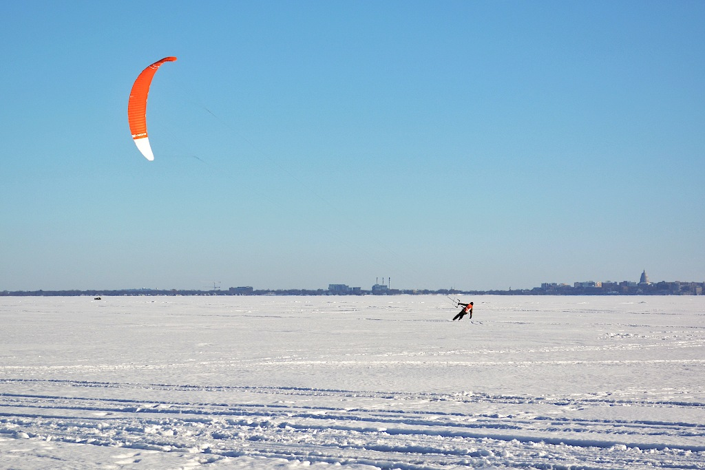 Person skiing on a frozen lake being pulled by a large kite flying overhead