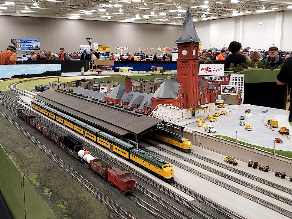 Model of a railroad station with tracks and trains along the side