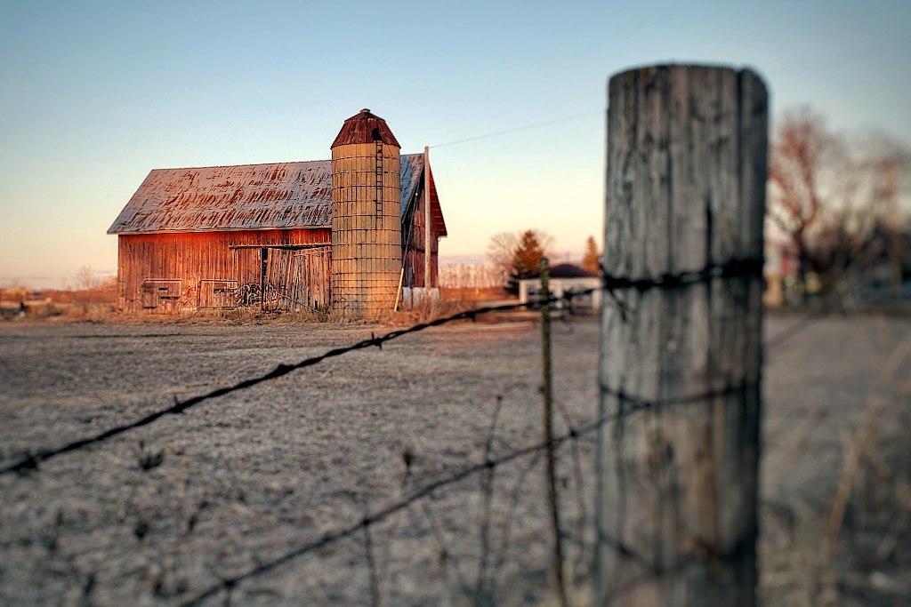 Barn and silo behind a barbed wire fence
