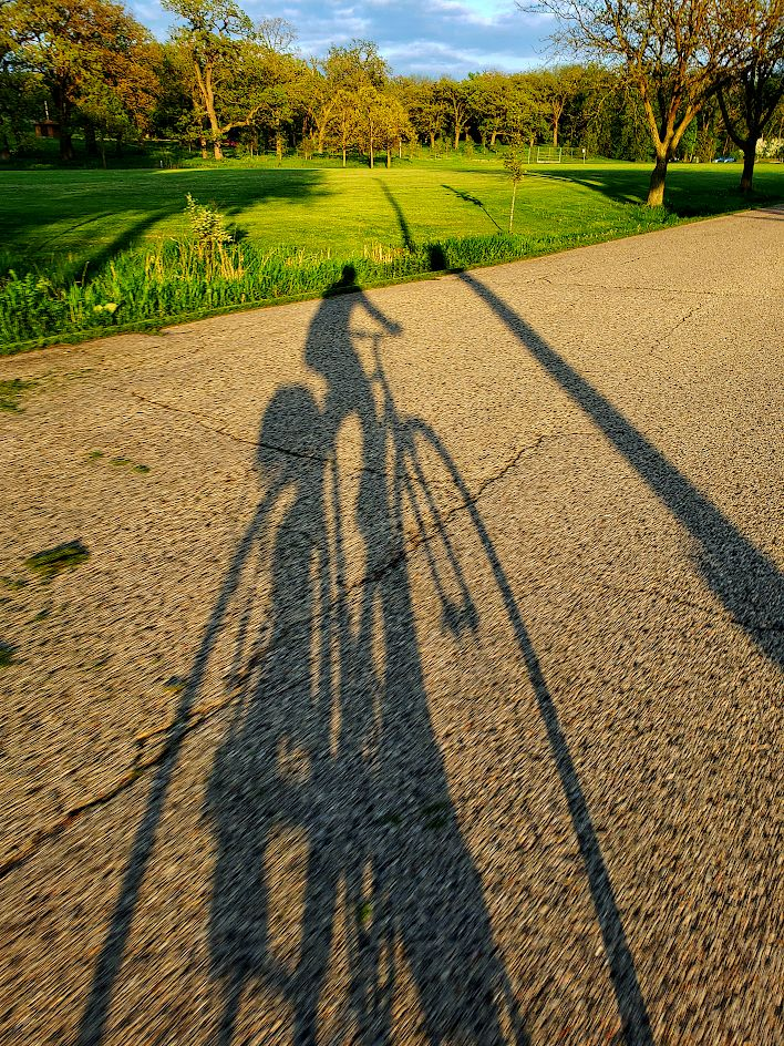 Long shadow of a bicyclist on a parkway road
